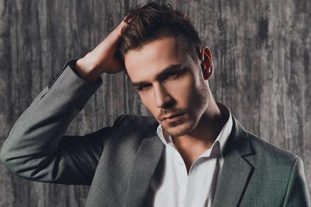 Aantrekkelijke stijve man in pak op de grijze achtergrond Stockfoto