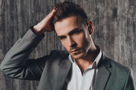 Attraktive starren Mann im Business-Anzug auf dem grauen Hintergrund Standard-Bild - 52888356