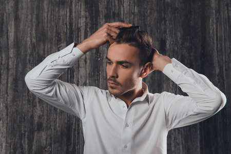 combing: Attractive rigid man combing hair on the grey background