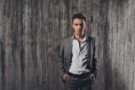 handome: Handome man in suit on the grey background with hands in pockets Stock Photo
