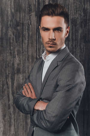 handome: Handome brutal man in suit on the grey background crossing hands