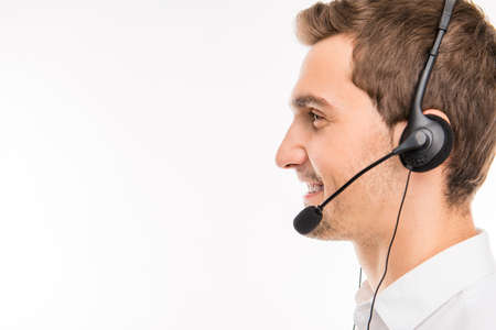 young boy smiling: a side-view portrait of young smiling agent of call-centre Stock Photo