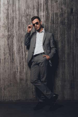 bel homme: Bel homme avec des lunettes tenant la main dans une poche sur le fond gris