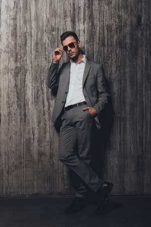 handsome business man: Handsome man with glasses holding hand in a pocket on the grey background