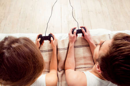 game: Happy couple in love playing video games with joysticks on the bed Stock Photo