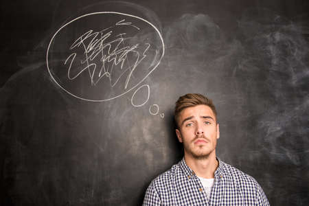 Young man against the background of chalkboard solving a problem Banco de Imagens