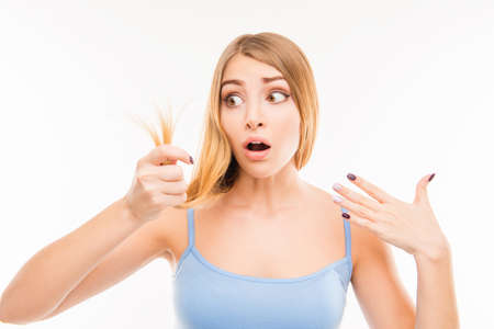 split ends: Young shocked woman looking at damaged split ends Stock Photo