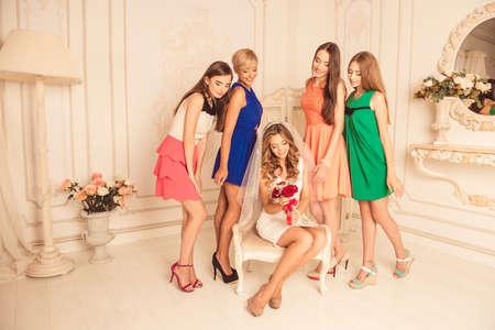 bridesmaids: Beautiful bridesmaids looking at the brides bouquet Stock Photo