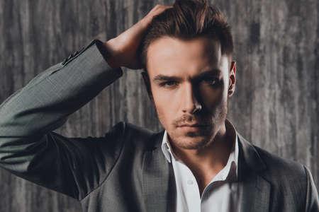 hombre atractiva atractiva en traje de negocios en el fondo gris Foto de archivo