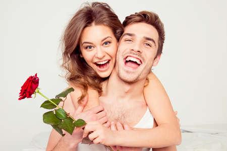 pareja en la cama: Alegre joven y la mujer en el amor que abraza en el dormitorio con la rosa