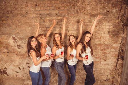 Schattige meisjes vieren kip-party met opgeheven handen en glaswerk Stockfoto