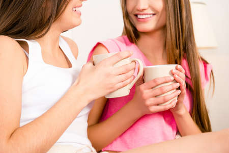 lesbo: Close up photo of two young girls holding cups with coffee Stock Photo
