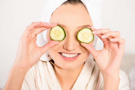 Nice young woman with cucumbers on eyes and towel on her head