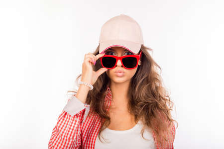 pouting: Young serious girl in pink hat touching her glasses and pouting