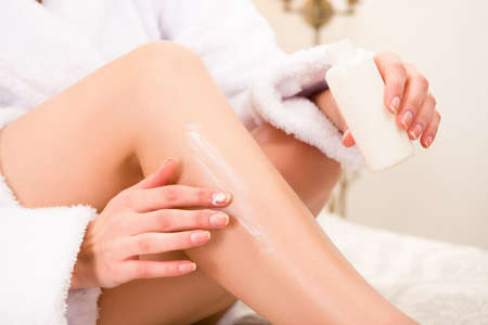 smearing: Closeup photo of young woman smearing cream on her leg