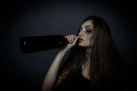 drinking problem: The social problem. Young unhappy woman drinking alcohol from a bottle