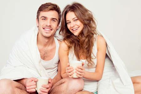 jovenes enamorados: Pareja feliz en el amor que se sienta en la cama con la manta y el caf� Foto de archivo