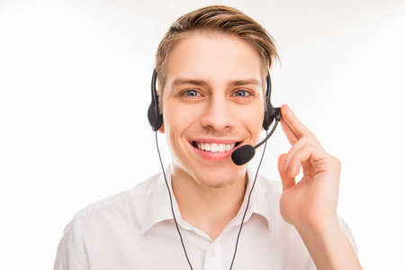 A close-up photo of smiling young agent of call centre touching head-phones