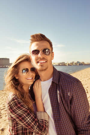 seaside: Smiling couple in love in spectacles  hugging on the seaside