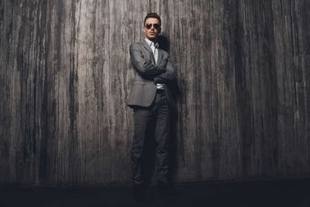 handome: Handome rigid man with glasses in suit on the grey background crossing hands