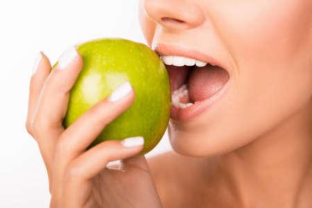 りんごをかじって美しい健康的な少女のクローズ アップ写真