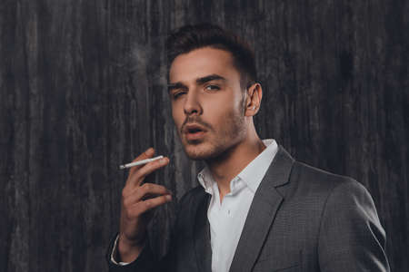 handome: Handome sexy man in suit on the grey background smoking a cigarette