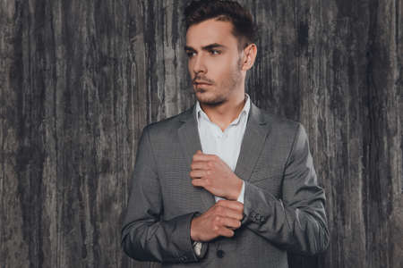 handome: Handome man in gray suit fastening buttons on the sleeves