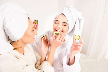 Funny young girls with towels on their heads feeding ech other with slices of cucumber