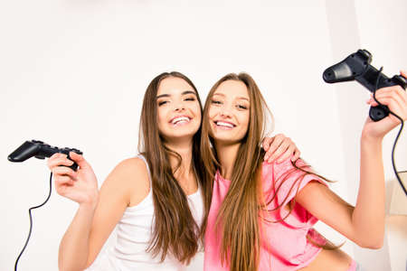 lesbo: Cheerful happy attractive girls playing video games at home Stock Photo