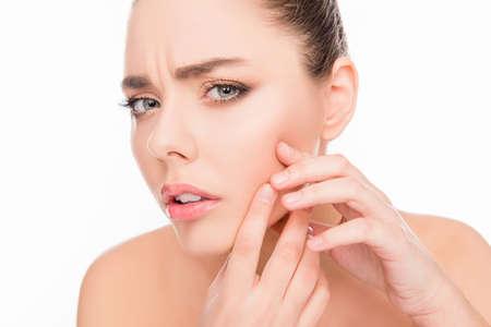 Portret van jonge aantrekkelijke vrouw aan haar gezicht te raken en op zoek naar acne