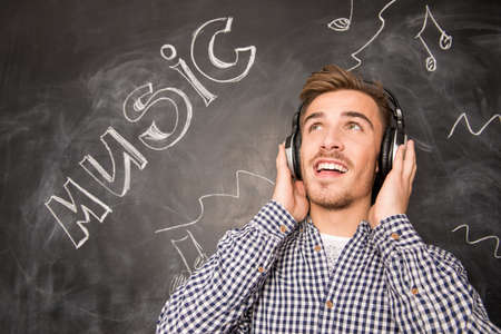 stubble: Young happy man listening to music on headphones against the background of chalkboard Stock Photo