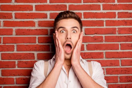 wonderment: Shocked young man touching his face on the background of wall