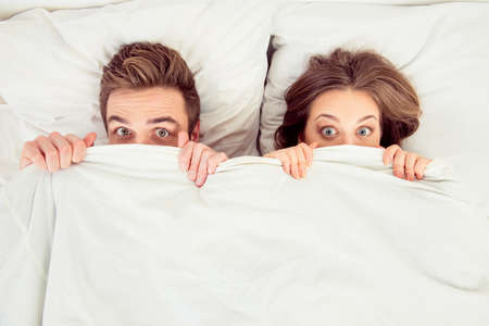 Surprised funny couple in love lying in the bed hiding themselves under blanket