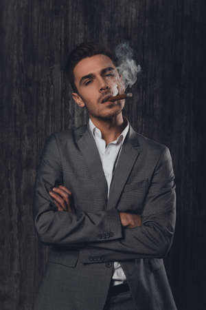 crossed cigarette: Handome brutal man in suit on the grey background crossing hands with a cigar