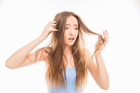 coiffeur: Sad pretty girl looking at her damaged hair Stock Photo