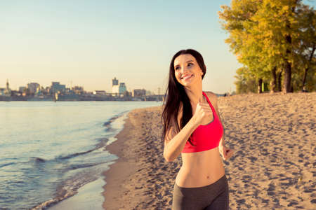 keep fit: Cute happy young girl running on the beach to keep fit Stock Photo