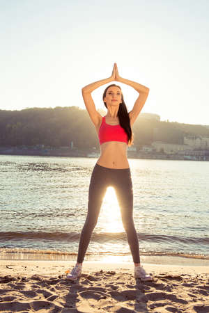 engaging: Healthy young slim girl  engaging yoga at the beach Stock Photo