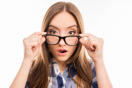 furor: Surprised pretty  girl taking off her glasses, close up photo