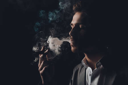 handome: Handome cheeky man in suit on the black background smoking a cigar