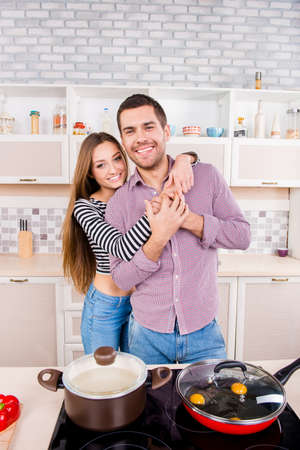 omlet: Cute couple in love making omlet and boiling soup in the kitchen