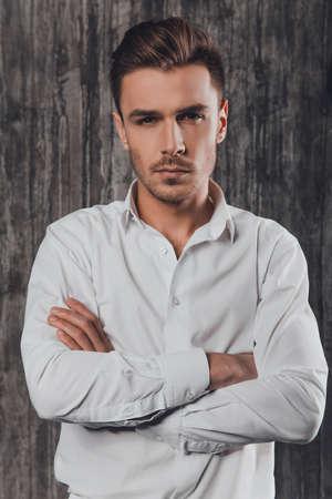 handome: Handome rigid man in white shirt on the grey background crossing hands Stock Photo