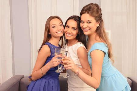 Tres muchachas del encanto felices que sostienen los vidrios con shampagne y sonriente