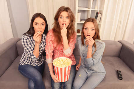 lesbo: Attractive scared girls watching film and eating popcorn