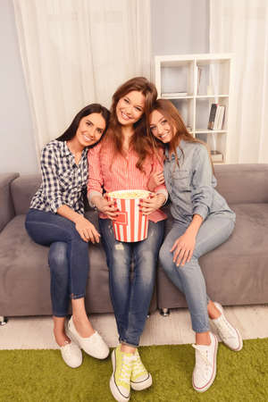 lesbo: Three happy women sitting on sofa and watching comedy with popcorn