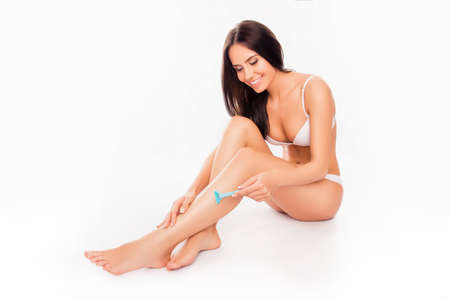 depilate: Portrait of young slim woman in white underwear shaving her leg