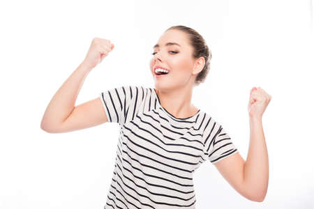 triumphing: Portrait of successful pretty girl triumphing with raised hands