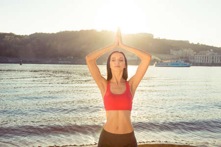 engaging: Attractive fit slim woman  engaging yoga at the seaside Stock Photo