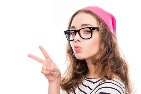 pouting: smiling girl in hat and glasses showing two fingers and pouting