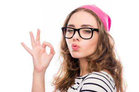 pouting: Portrait of  smiling girl in hat and glasses gesturing OK and pouting