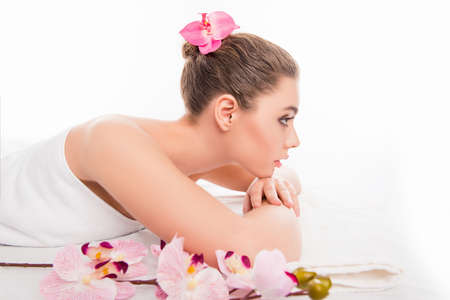 sauna nackt: Pretty young girl lying in spa and relaxing with orchid